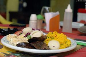 prato de avestruz com ervas, arroz de açafrão, farofa de ovo e salada de palmito